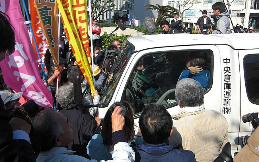 Protesters opposing a new Marine Corps runway in Henoko, Okinawa, surround a van on Dec. 27, 2011, preventing a delivery of an environmental impact assessment report to Okinawa prefectural government. The report submission is a necessary procedure under Japanese environmental law. Tokyo is moving forward with the construction of V-shaped runway, planned to extend into reclaimed land in Henoko Bay, adjacent to Camp Schwab.