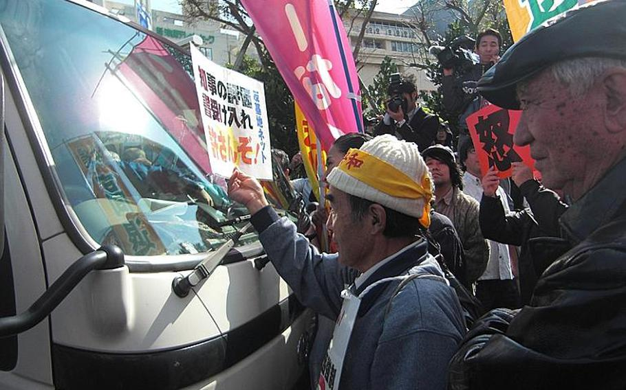 """An anti-military activist flashes a card Dec. 27, 2011, that reads """"We won't let you deliver an environmental report to Governor."""" About 100 protesters surround a carrier service van that carries the report at the prefectural government office, sending the vehicle away without making delivery."""