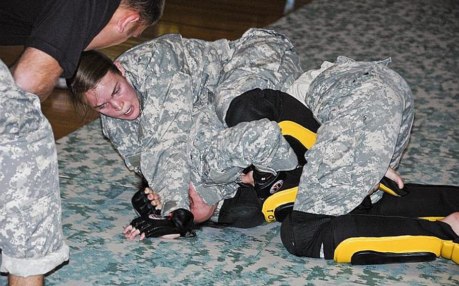 Staff Sgt. Quail Hjelmeir, top, grapples with Spc. Melissa Myers during a U.S. Army Combatives tournament at Camp Zama in December 2011. Myers defeated Hjelmeir to win the flyweight division.