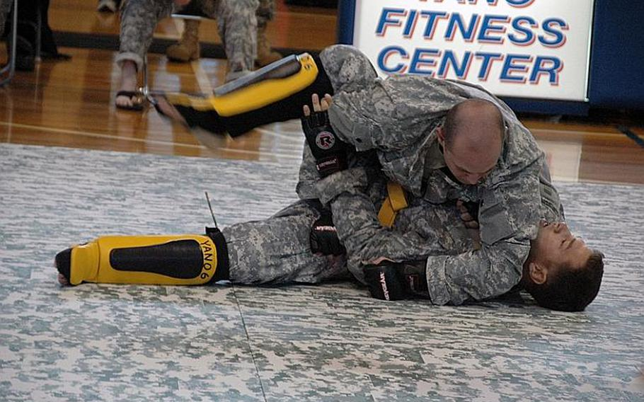 Sgt. Maximillan Curtner, top, wrestles Staff Sgt. Christopher Hogan during an Army Combatives tournament at Camp Zama in December 2011. Curtner finished second in the heavyweight division while Hogan placed third.