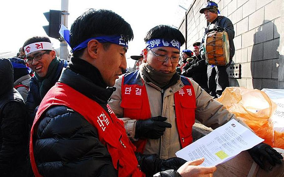 Former security guard Chon Woo-nam, front left, examines a proposed contract on Jan. 11, 2012, from G4S, the company responsible for providing guards for entry points at most U.S. military installations in South Korea. Since G4S' contract went into effect in December 2011, many guards for the previous security guard company have refused to work for G4S because of disputes over working hours and pay.