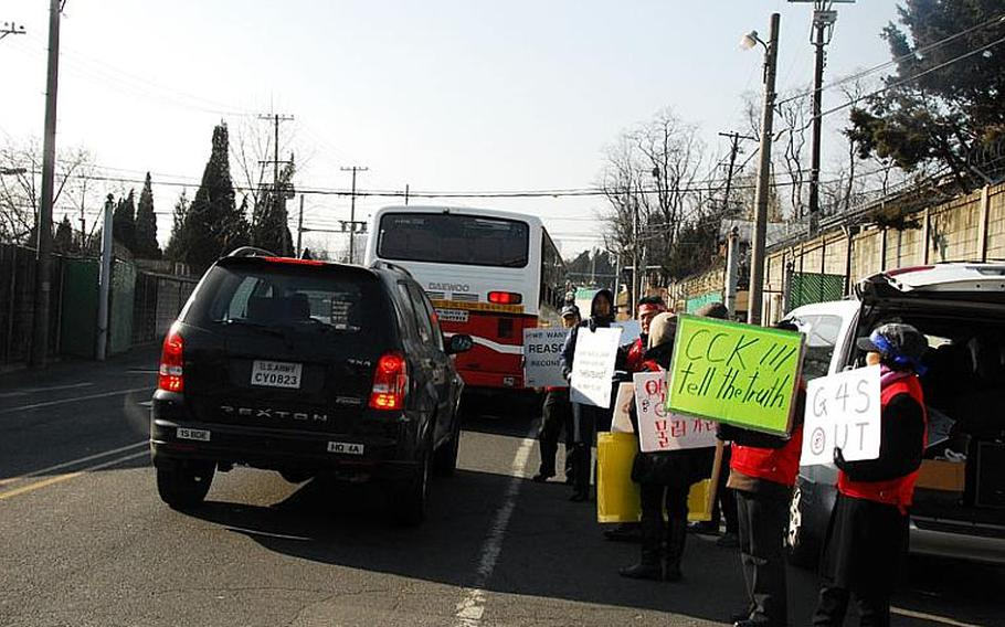 Former security guards hold up signs as cars enter U.S. Army Garrison-Yongsan on Jan. 11, 2012. Hundreds of former security guards have refused to work for G4S, the contractor responsible for providing security at entry points at most U.S. military installations in South Korea, since the company's contract went into effect last month.