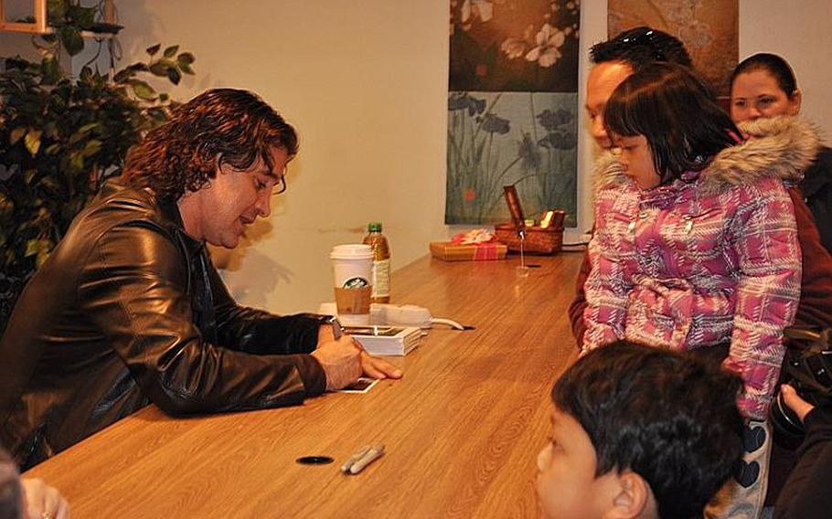 Scott Stapp, the lead singer of Creed, signs autographs for Petty Officer Li Tamondong and his children, Theresa May and Mikael at the Yokosuka United Service Organizations office on March 18, 2012. Stapp and his wife, Jaclyn, said they wanted to thank the servicemembers for their relief efforts during Operation Tomodachi.