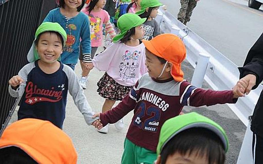 Children from local daycare centers walk through Camp Foster's commissary gate to the Shoppette gate during a Nov. 5, 2012, disaster drill on the Marine Corps base.  In the wake of March 11, 2011 earthquake in Japan?s northern region, securing evacuation routes for residents in Okinawa?s waterfront neighborhoods has a priority.