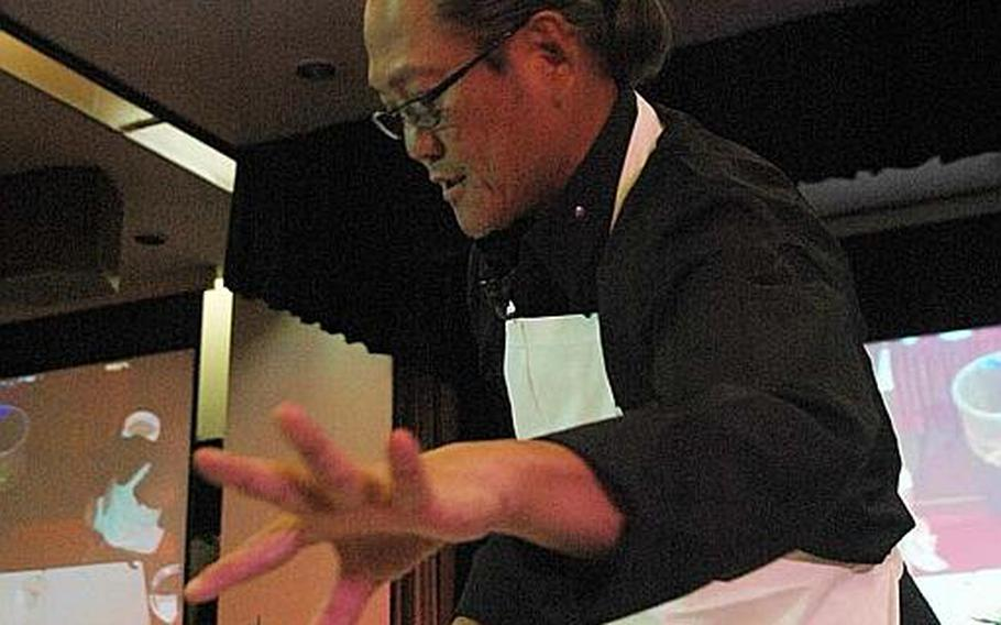 """Iron Chef"" Masaharu Morimoto goes for a sprig of daikon radish during a cooking demonstration Nov. 4, 2012, at Yokota Air Base, Japan."