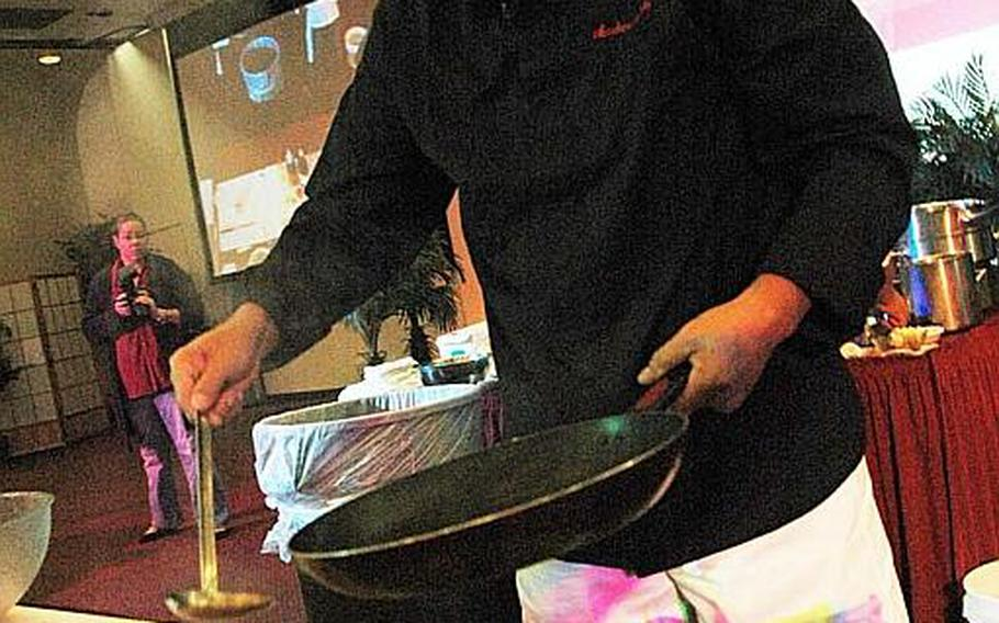 """""""Iron Chef"""" Masaharu Morimoto drizzles scorching hot sesame oil over thin strips of raw fish to before serving during a cooking demonstration Nov. 4, 2012, at Yokota Air Base, Japan."""