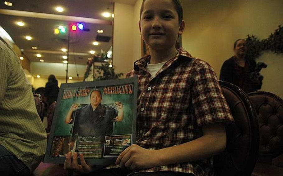 """Joshua Rennekamp, a fourth-grader from Yokota Air Base, Japan, displays an autographed photo of """"Iron Chef"""" Masaharu Morimoto after a demonstration Nov. 4, 2012, by the world-renowned chef."""