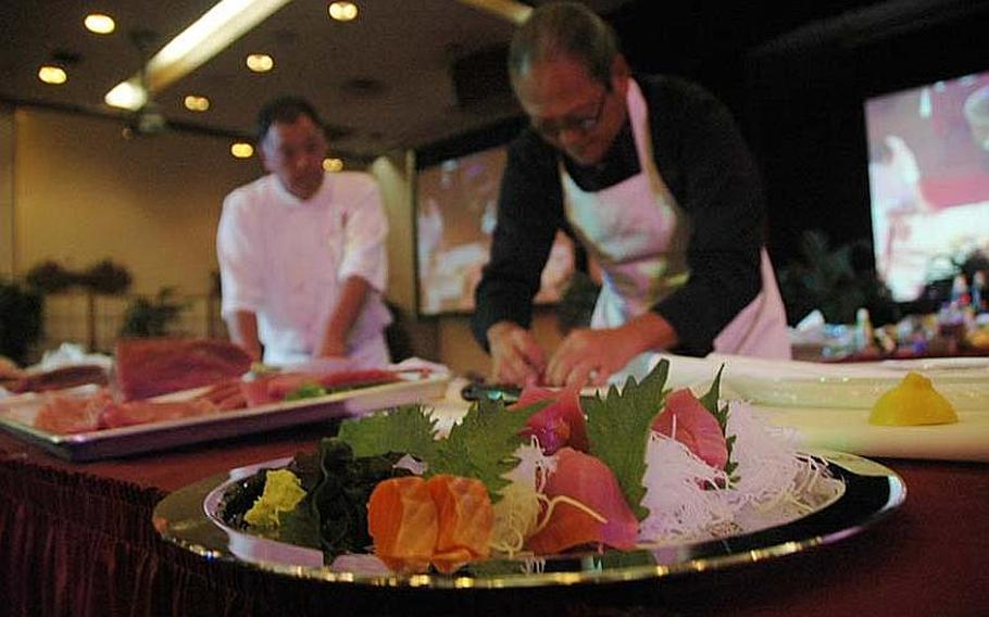 """""""Iron Chef"""" Masaharu Morimoto prepares a variety of tuna dishes Nov. 4, 2012, at Yokota Air Base, Japan, during a cooking demonstration for base cooks and novice chefs."""