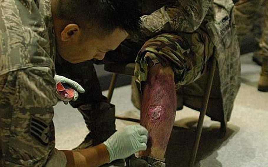 Staff Sgt. Don Flores applies moulage make-up to Airman 1st Class Benjamin Bell before a mock disaster exercise at Yokota Air Base, Japan, on Nov. 6, 2012. The U.S. military trains troops in the art of moulage, a French term for applying mock injuries for emergency response training.