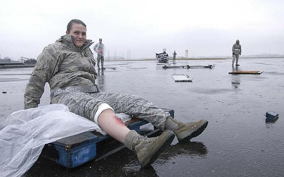 Senior Airman Amanda Kelly waits in the rain with a simulated broken tibia on Nov. 6, 2012, during a mock disaster exercise at Yokota Air Base, Japan.