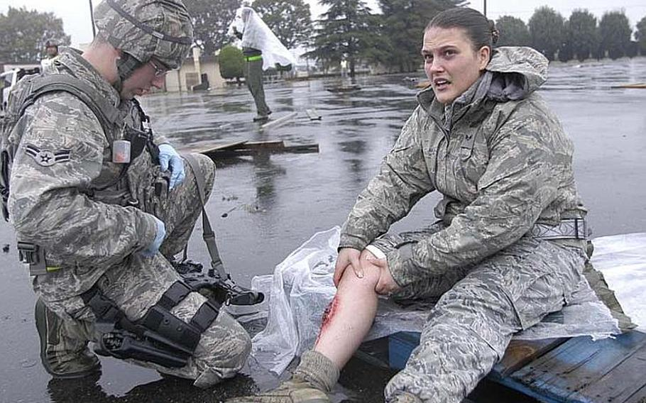 An airman first class from the 374th Security Forces Squadron comes to the aid of Senior Airman Amanda Kelly who grips her simulated injury -- a broken tibia -- during a mock disaster exercise on Nov. 6, 2012, at Yokota Air Base, Japan.