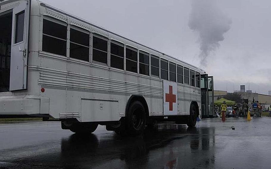 """An ambulance bus waits on the flight line on Nov. 6, 2012, during a during a disaster response training exercise at Yokota Air Base, Japan. The """"am bus"""" is a passenger bus fitted with emergency medical equipment used to transport multiple patients."""