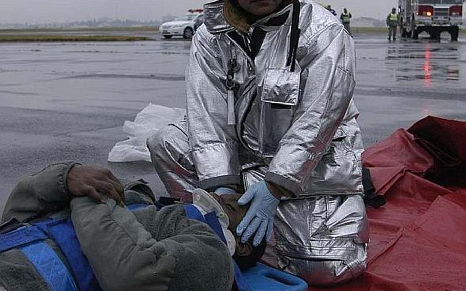 A Japanese firefighter from Yokota Air Base, Japan, stabilizes Senior Airman Anthony Washington during a mock disaster exercise at the base on Nov. 6, 2012. The scenario revolved around a tornado hitting the base.