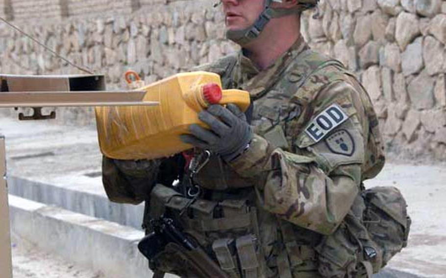 Sgt. B-Wesley Sanders, 25, of Corpus Christi, Texas, who is working with the 630th Ordnance Company out of Fort Riley, Kansas, retrieves a container of homemade explosive from a street in Qalat, Zabul Province, Afghanistan in September.
