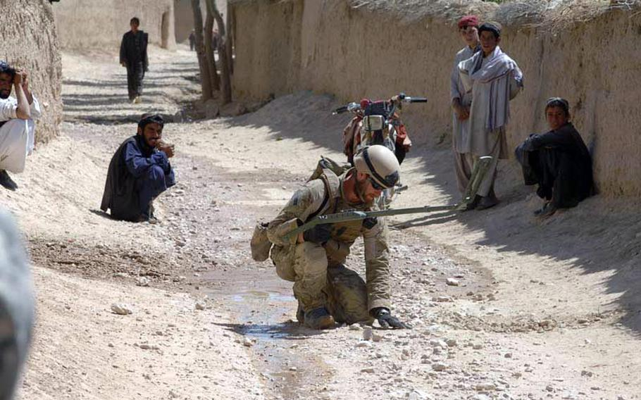 A Navy explosive ordnance disposal technician searches for a bomb in Zabul Province, Afghanistan in September 2010.