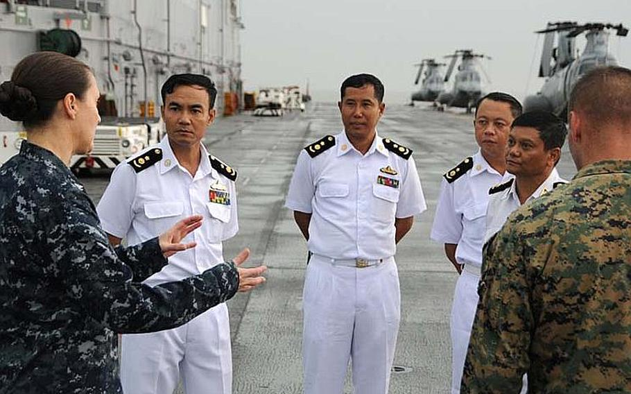 Capt. Heidi Agle, left, deputy commodore of Amphibious Squadron Eleven, discusses the USS Bonhomme Richard's flight deck during a tour for Myanmar naval officers on Nov. 18, 2012, in the Andaman Sea. The tour preceded President Barack Obama's speech in Myanmar's commercial capital of Yangon on Monday. Although sanctions from Washington prevent a large-scale relationship between the two militaries, the two countries are exploring academic and small-group exchanges.