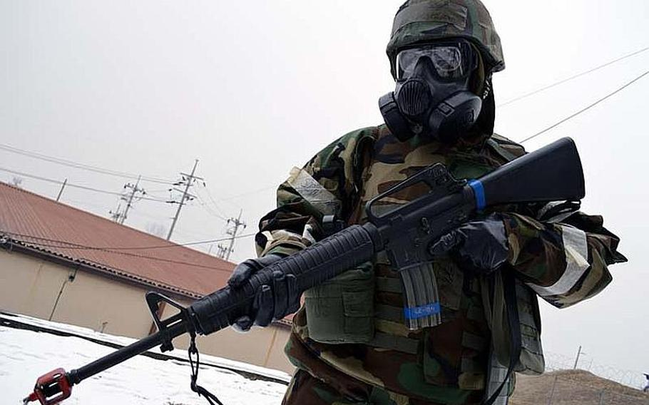 Staff Sgt. Beniteau Fenelus walks on patrol with his M-16 around Osan Air Base, South Korea, during the Beverly Midnight exercise. Fenelus and other Osan airmen wore their his full Mission Oriented Protective Posture (MOPP) gear during the simulated war-time exercise.