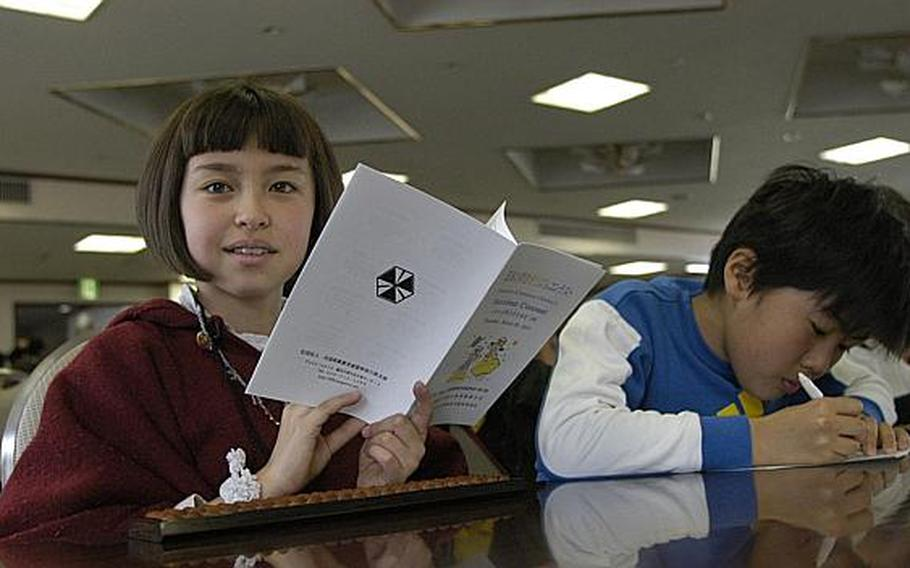 Klara Enriquez, a fourth-grader at Shirley Lanham Elementary School, takes a quick break from reading the program for the March 28, 2013, soroban event where American students and Japanese students showed off their abilities to manually computer complex series of numbers.