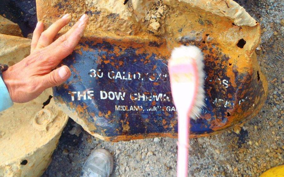 A Japanese worker brushes away dirt from one of 16 barrels unearthed in Okinawa City on June 13, 2013. The city called for Tokyo to investigate for Agent Orange, but manufacturer Dow Chemical Company denied the drums contained the herbicide.
