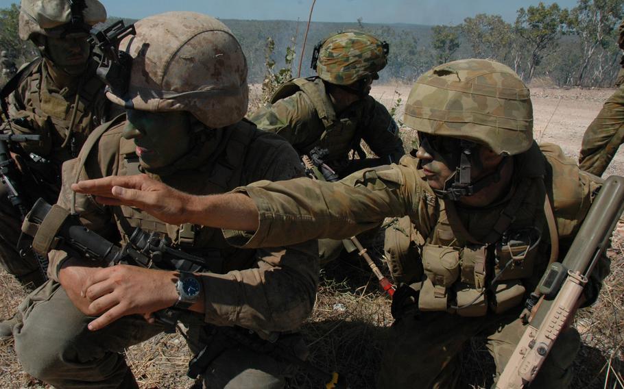 U.S. Marine 1st Lt. Mike Kopa, 26, of Woodbridge, Va., second from left, gets some advice from an Australian soldier at Mount Bundey Training Area, Australia in June.