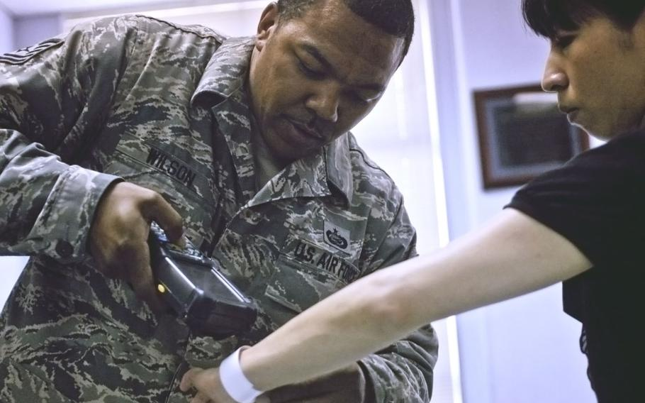 Tech. Sgt. Charles Wilson, a member of the individual personnel readiness section, scans an identification wristband during an exercise at Yokota Air Base, Japan, July 15, 2013.  Eric Guzman/Stars and Stripes