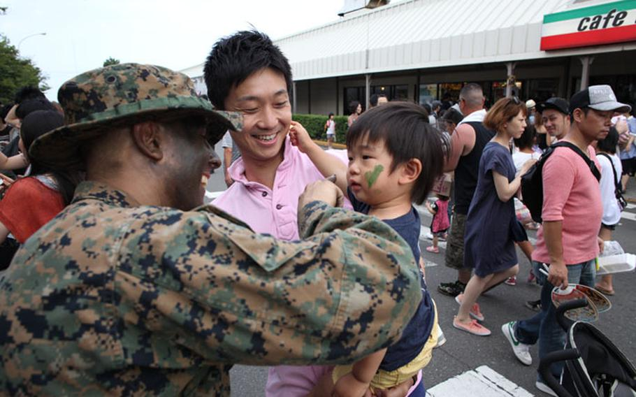 A Marine paints a Japanese boy's face with camouflage at the 37th annual Yokosuka Friendship Festival on Aug. 3, 2013. The Navy base was open to the Japanese public who were treated to live entertainment, food vendors and other events.