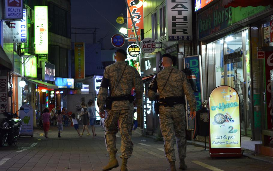 Members of the Osan Air Base joint town patrol walk on of the streets at the Songtan Entertainment District, just outside the front gate of the base in South Korea on Aug. 17, 2013. Base officials in recent months have systematically been putting the notorious base-area juicy bars off-limits to U.S. servicemembers.