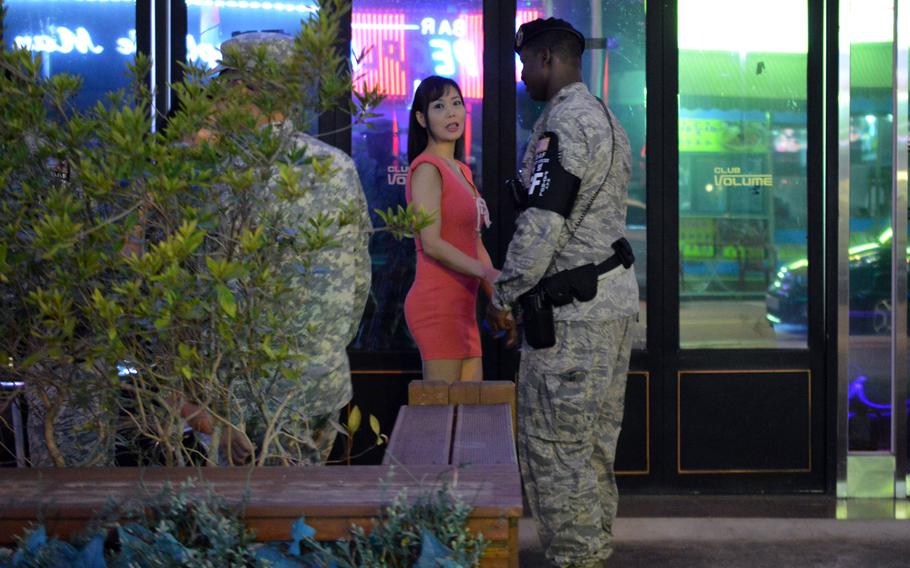 Members of the Osan Air Base joint town patrol speak with employees outside a bar in the Songtan Entertainment District in South Korea, Aug. 17, 2013. Base officials say they hope in the next two months to have all juicy bars in the entertainment district just outside the front gates of Osan Air Base either off-limits to servicemembers or remade into different types of establishments.