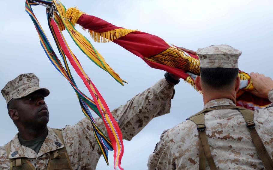Sgt. Maj. Devon Lee, the sergeant major of Marine Medium Tiltrotor Squadron 262, helps unveil the squadron's new battle colors in a ceremony aboard Marine Corps Air Station Futenma, Okinawa, Aug. 30, 2013.