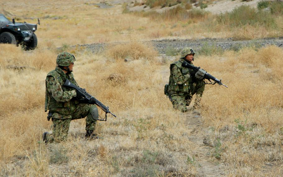 In this file photo from Sept. 17, 2103, Japanese Ground Self-Defense Force soldiers kneel as they wait for movement orders during a platoon live-fire training exercise at Yakima Training Center, Wash. The joint U.S.-Japanese exercise was part of Operation Rising Thunder.