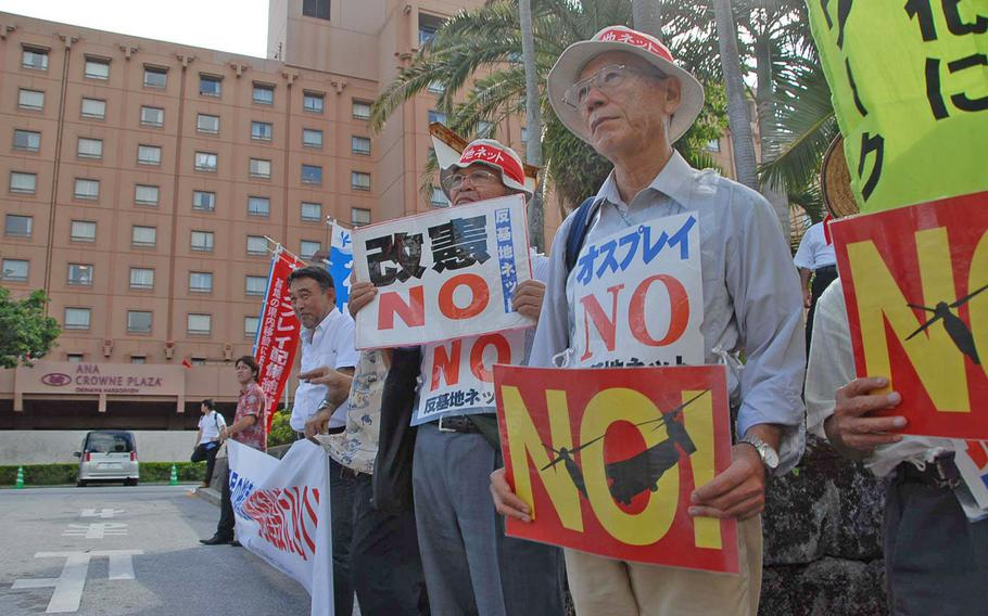 Okinawans opposed to the U.S. military picket Oct. 8 outside a hotel where the prefecture's governor and ministers from Tokyo met to discuss the relocation of Marine Corps Air Station Futenma.