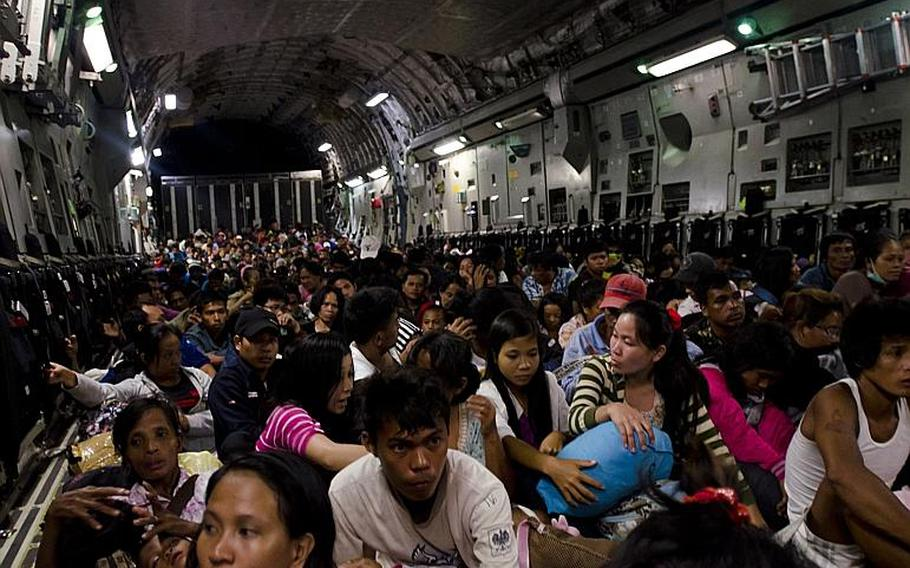 Victims affected by Super Typhoon Haiyan wait aboard a C-17 aircraft provided by the United States military as they prepare to leave Tacloban, Philippines for Villamore Airbase in Manila.