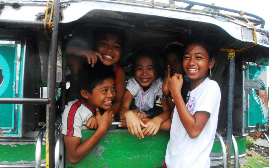Children shelter from rain inside a Jeepney in Guiuan last Friday. Officials there say locals are resilient despite the fact that most of their homes were destroyed or damaged by Typhoon Haiyan.