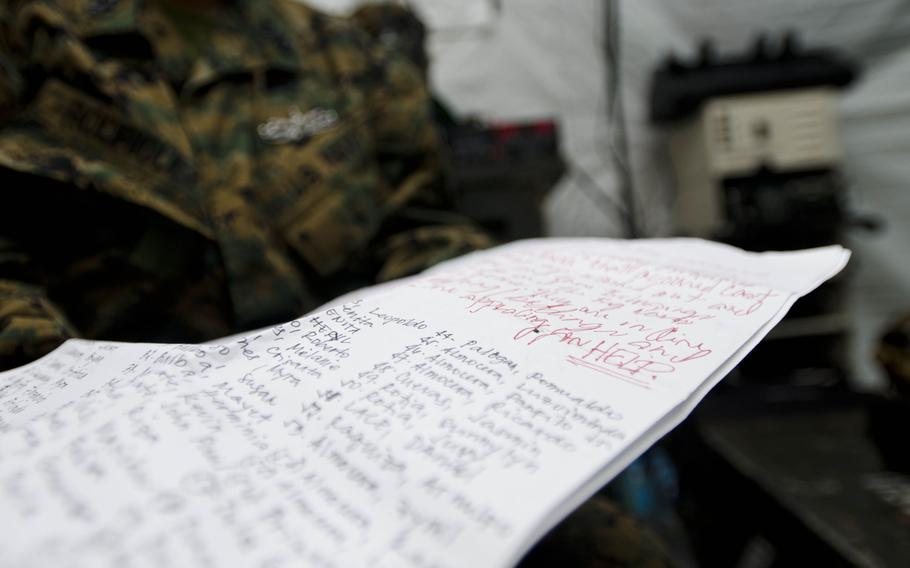 Navy Sr. Chief Vilma Rodriguez, a native of Tacloban, Philippines, holds a plea signed by nearly 200 people living in Tacloban requesting assistance and relief supplies in the wake of Super Typhoon Haiyan.