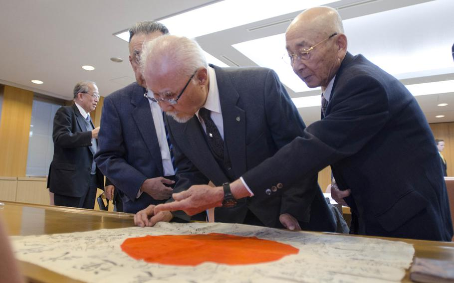 Japanese officials from Shizuoka, Japan, inspect markings on a flag from World War II that was returned to Japan on Dec. 6, 2013.