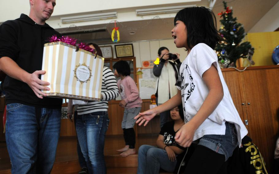 Children celebrate their gifts from the Marines and family members of 3rd Intelligence Battalion during a Christmas gift giving at the Nagomi Nursing Home for Children in Kin, Okinawa, Dec. 23, 2013.   Lisa Tourtelot/Stars and Stripes