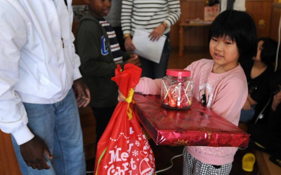 Sgt. Marvin Prince, and intelligence analyst with 3rd Intelligence Battalion, delivers gifts to children at the Nagomi Nursing Home for Children in Kin, Okinawa, Dec. 23, 2013.   Lisa Tourtelot/Stars and Stripes