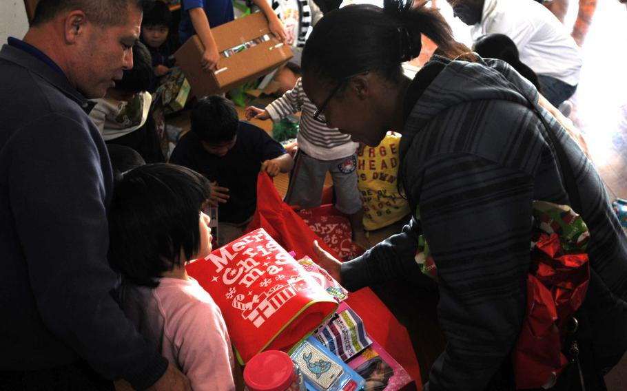 Lance Cpl. Jessica Nelson, right, a topographic analyst with 3rd Intelligence Battalion, helps children unwrap their gifts at the Nagomi Nursing Home for Children in Kin, Okinawa, Dec. 23, 2013.   Lisa Tourtelot/Stars and Stripes