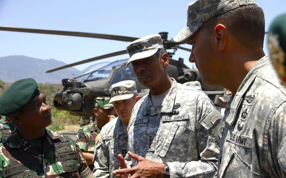 U.S. Army Pacific commander Gen. Vincent Brooks talks to Indonesian army officers about Apache attack helicopters during a tour of Garuda Shield exercise equipment on Sept. 24, 2014, on Java Island. In the background is one of four Apaches brought to Indonesia for the exercise, which is the first leg of Pacific Pathways.