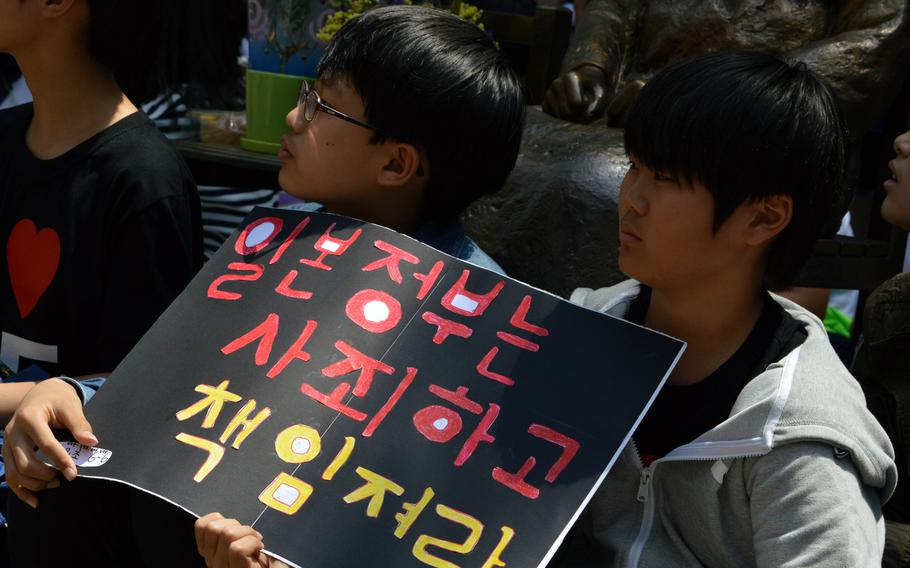 Korean children hold a sign during a protest across the street from the Japanese Embassy in Seoul, South Korea, on May 21, 2014. A protest is held every Wednesday over the issue of Korean women forced into sexual slavery by Japan during World War II.