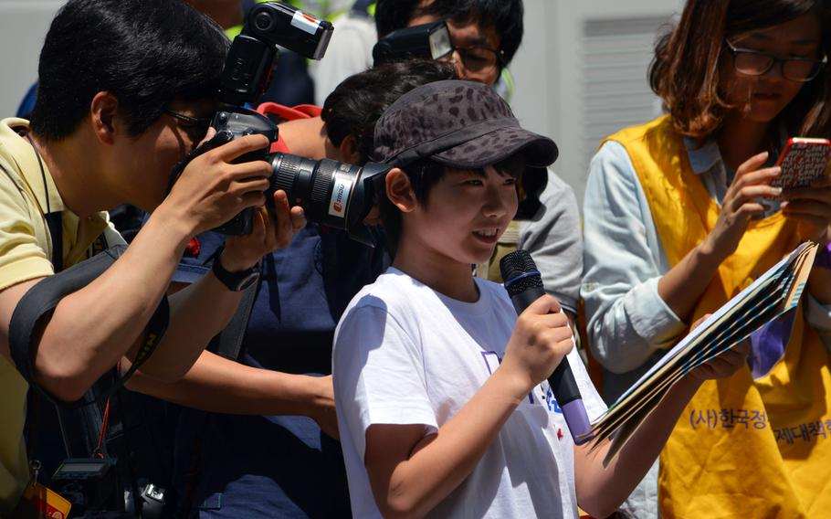 A Korean child speaks during a protest speaks during a protest across the street from the Japanese Embassy in Seoul, South Korea, on May 21, 2014. Members of the media close in to take photos of his speech during the protest of Japan forcing Korean women into prostitution during World War II.