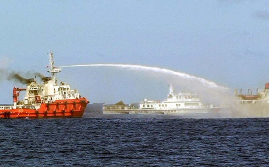 In this file image from Wednesday, May 7, 2014, a Chinese ship, left, shoots a water cannon at a Vietnamese vessel, right, while a Chinese coast guard ship, center, sails alongside in the South China Sea, off Vietnam's coast.