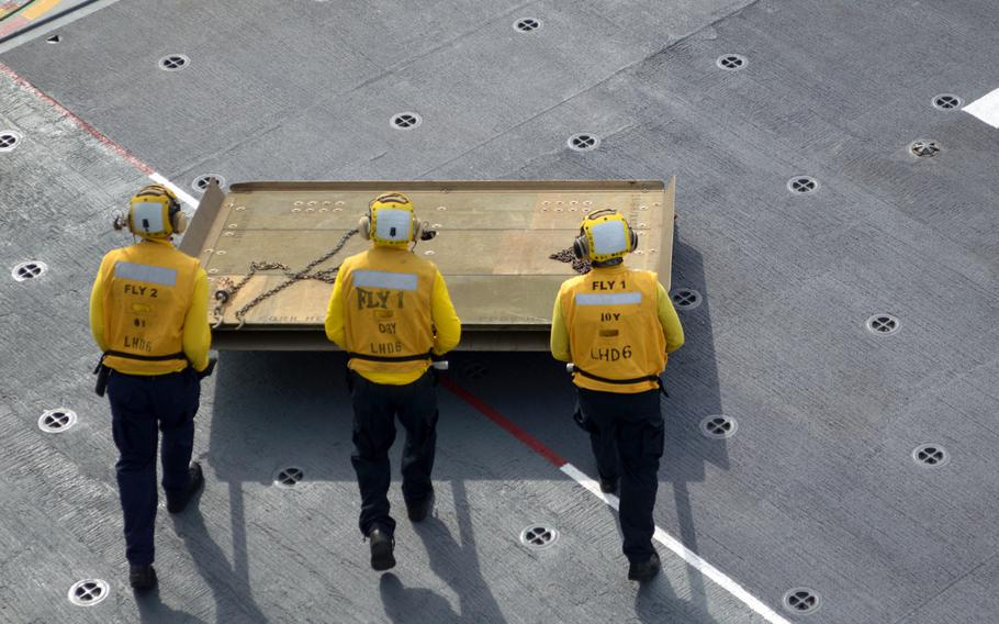 Deck crew of the ROKS Dokdo push a heat shield to a U.S. Marine Corps MV-22 Osprey on March 26, 2015. The shield was necessary to prevent deck damage from the Osprey's exhaust.