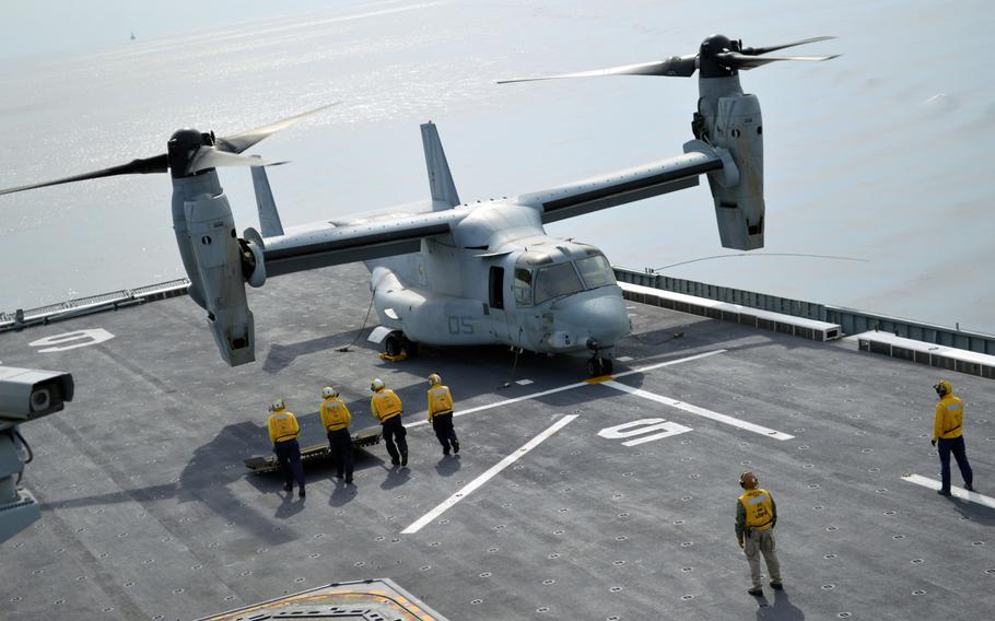 Deck crew of the ROKS Dokdo push a heat shield to a Marine MV-22 Osprey on March 26, 2015. The shield was necessary to prevent deck damage from the Osprey's exhaust.