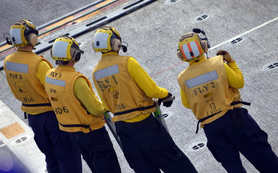 Crewmen of the ROKS Dokdo stand on deck to observe a Marine MV-22 Osprey on March 26, 2015. The South Korean sailors worked to tie down and then release the U.S. Marine Corps aircraft.
