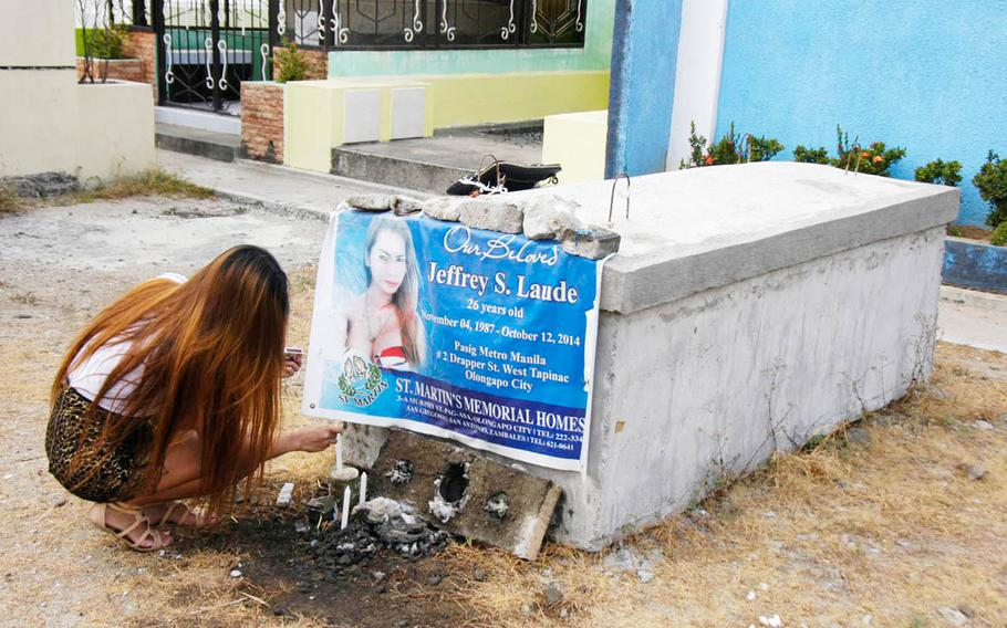 A Filipina transgender woman who shared an apartment with Jennifer Laude lights candles at her late friend's tomb at a cemetery in Olongapo, Philippines, in March 2015. Laude was found dead in an Olongapo hotel Oct. 11, 2014, after checking into a local hotel with a U.S. Marine, authorities say.