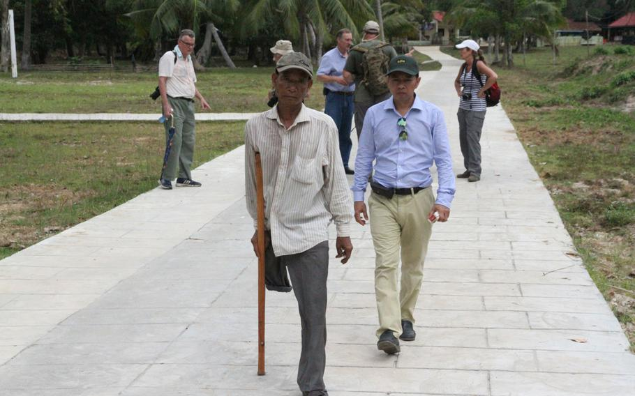 Em Son, left, former Khmer Rouge commander of Koh Tang during the May 15, 1975, Vietnam War battle, arrives at the dedication of plaques to honor the fallen from both sides during a May 12, 2015, ceremony commemorating the 40th anniversary of the battle.