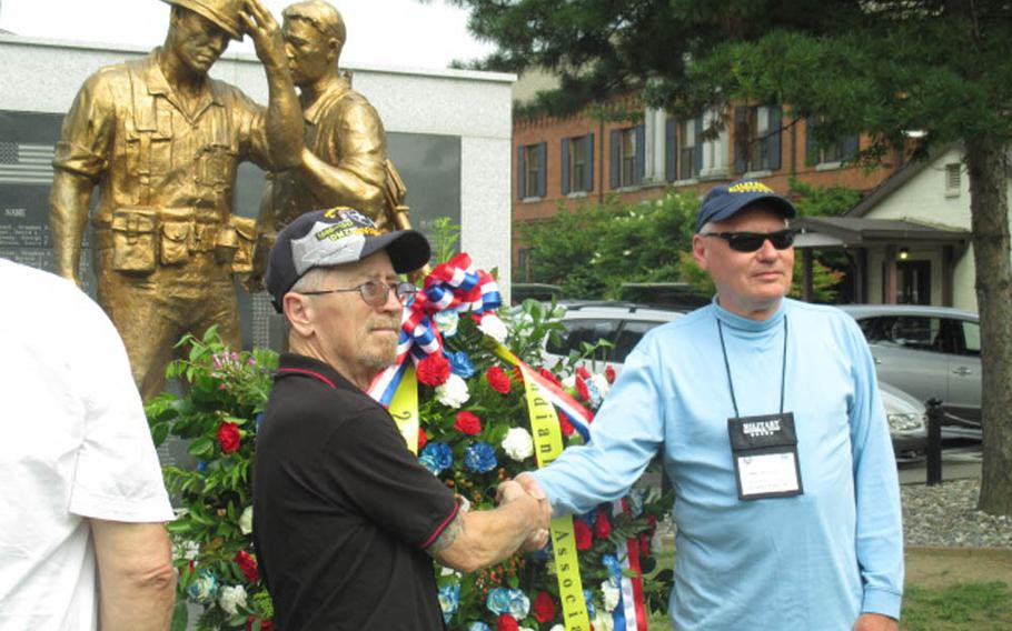 Bob Haynes, left, and John Batty-Sylvan, right, both former 2nd Infantry Division soldiers who served in South Korea during the 1960s, pose Monday, June 29, 2015, in front of a memorial at U.S. Army Garrison Yongsan. The memorial honors U.S. and South Korean troops killed in combat since the end of the Korean War. Haynes and Batty-Sylvan are part of a veterans group that traveled to South Korea to take part in 50th anniversary celebrations this week of 2ID's presence on the peninsula.