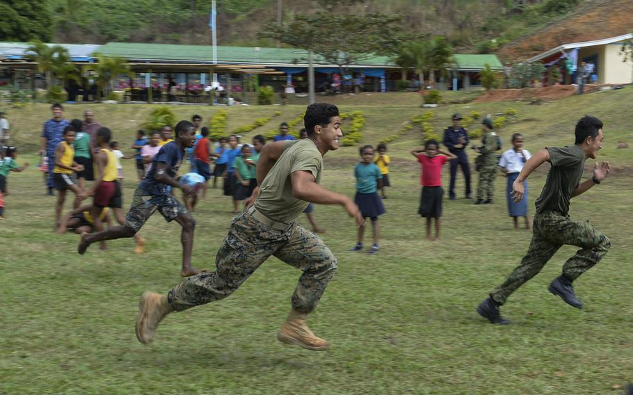 Cpl. Lucas Ferreira participates in a relay race at the Viani Primary School in Fiji during Pacific Partnership, June 17, 2015.