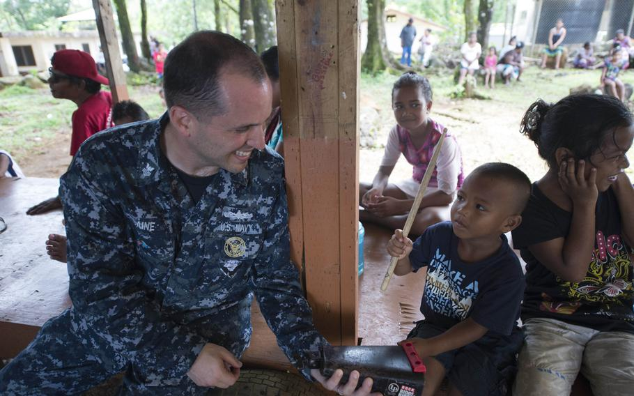 Musician 1st Class David Baine teaches a boy from the Federated States of Micronesia to play the cowbell during the USNS Millinocket's second stop in Pacific Partnership, June 25, 2015.
